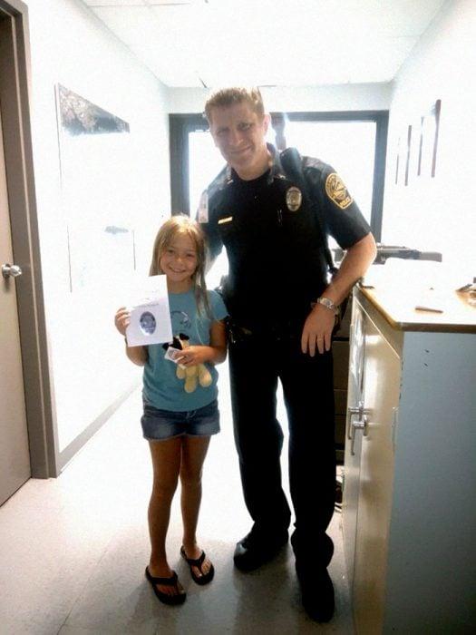 niña rubia junto a policía