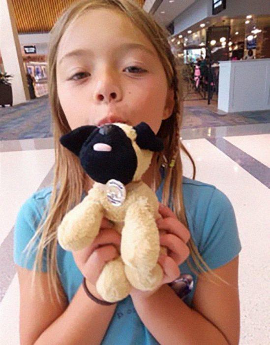 niña rubia con perro de peluche