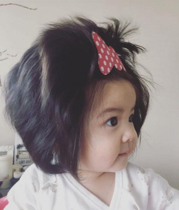bebé con moño en la cabeza