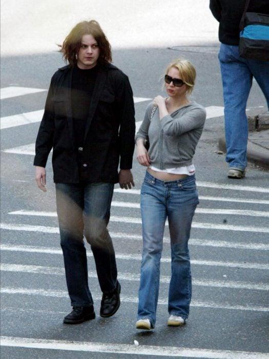 hombre con cabello largo negro y mujer rubia con lentes