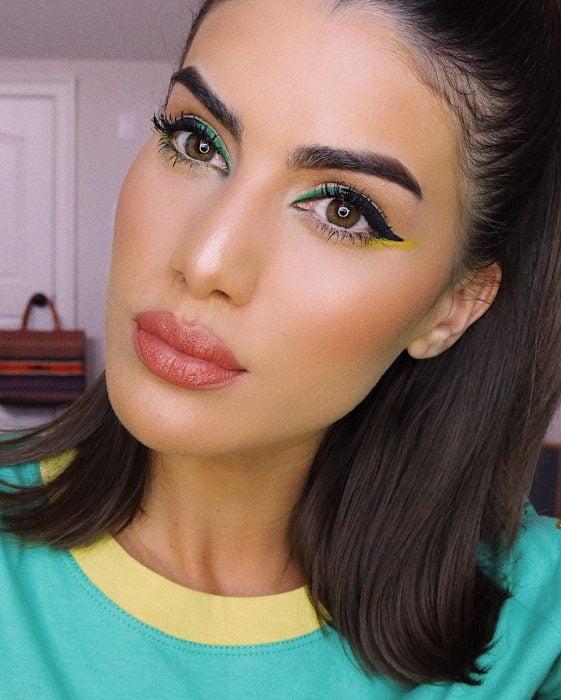 mujer morena con delineado verde con amarillo