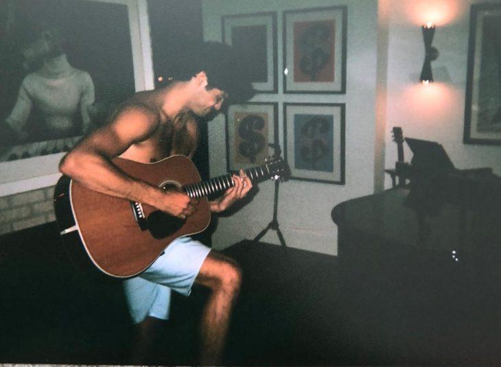 hombre con short y tocando la guitarra