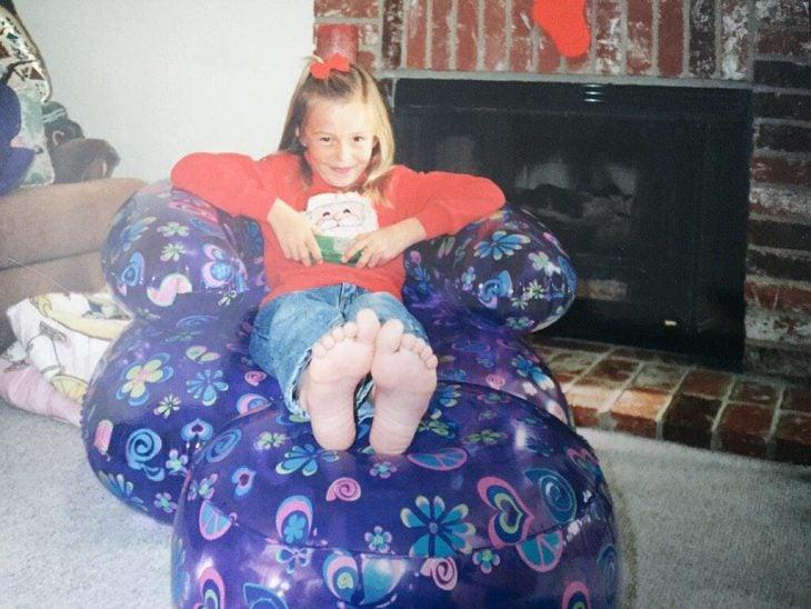 niña sobre un sillón inflable de plástico