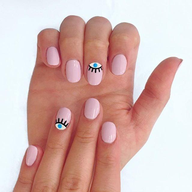 Uñas cortas en color rosa con un hojo