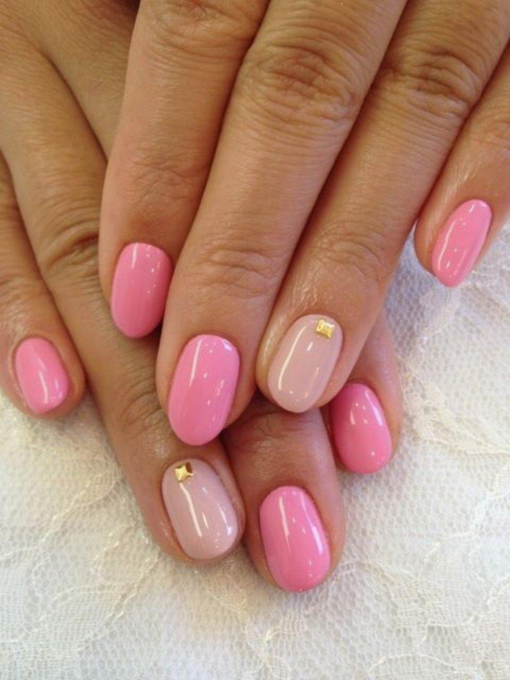 Uñas cortas en color rosa con piedras doradas