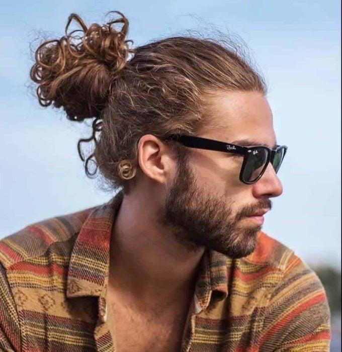 hombre con chongo y cabello rizado
