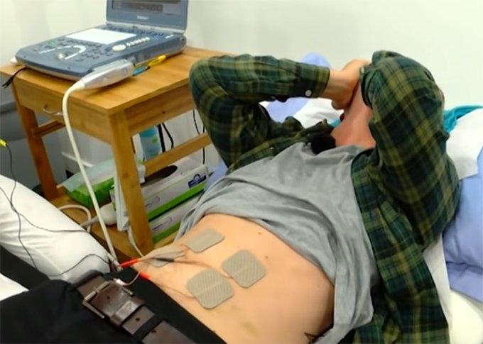 Hombre recostado en una camilla experimentando los dolores del parto