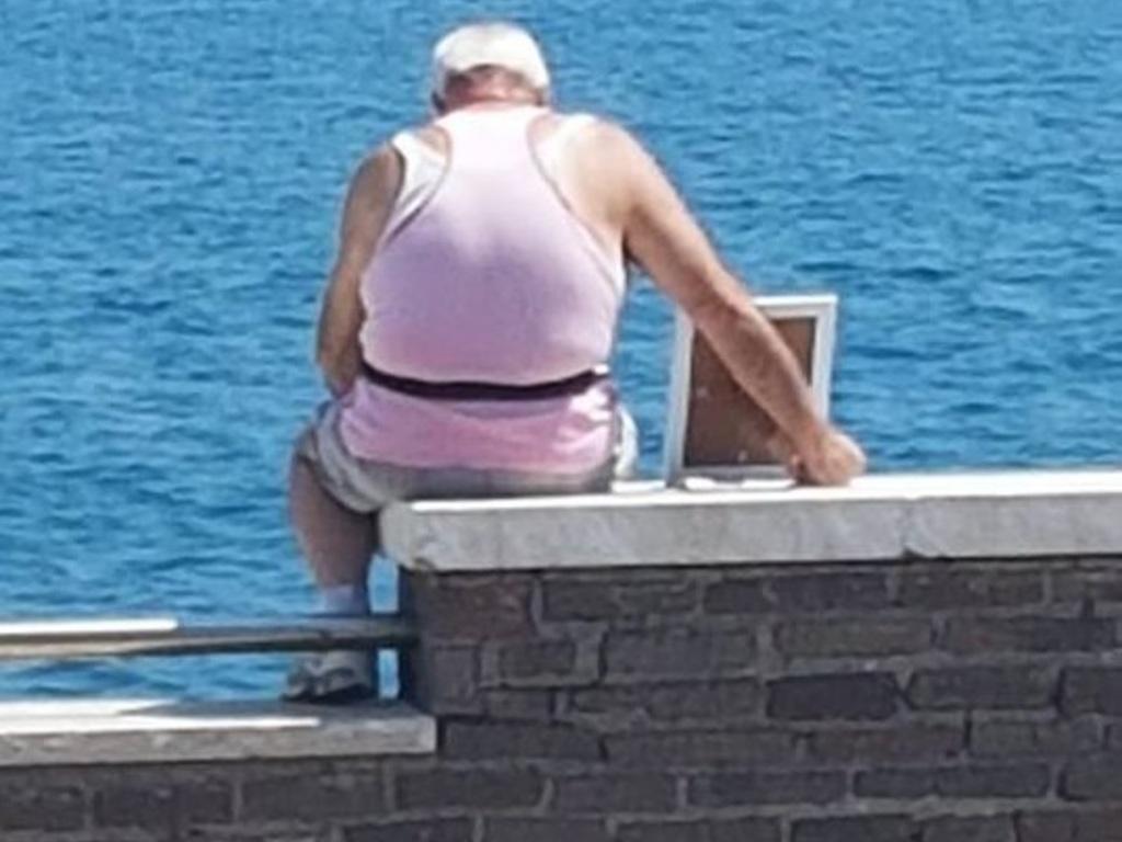 Hombre lleva la foto de su esposa mar