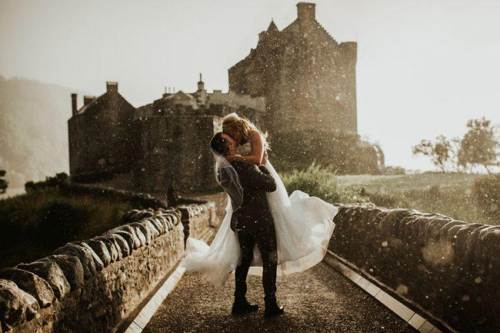 Pareja de novios en un callejón besándose durante una sesión de fotos el día de su boda
