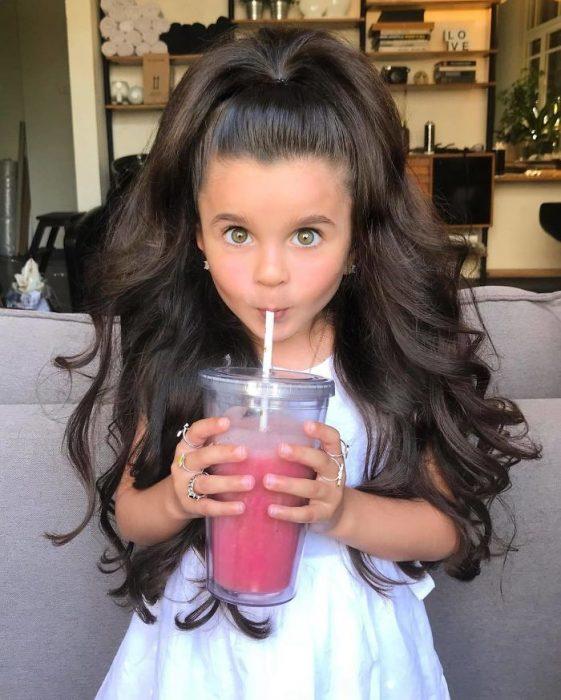niña bebiendo licuado rosa