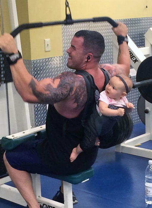Hombre haciendo ejercicio con un bebé en la espalda