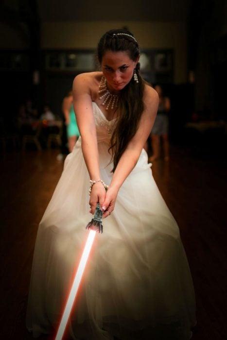 Novia sosteniendo un sable de luz de star wars