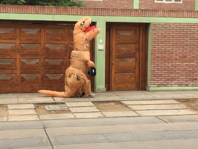 Papá e hijo caminando por la calle vestidos de dinosaurios