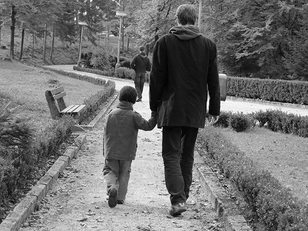Papá e hijo caminando tomados de la mano por un sendero