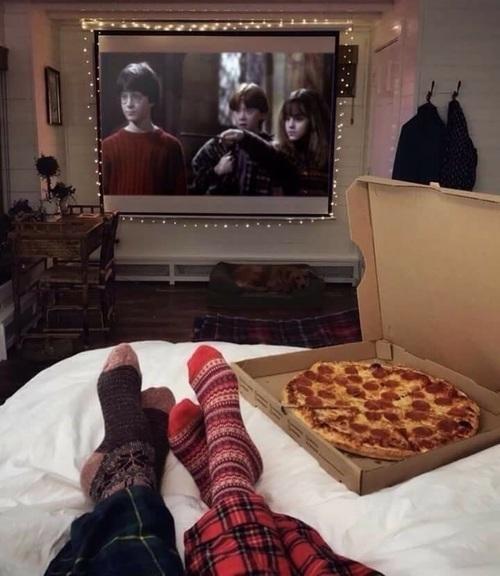 Pareja de novios viendo una película y comiendo pizza