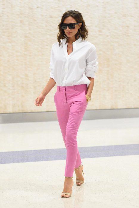 Victoria Beckham usando un pantalón rosa y camisa blanca
