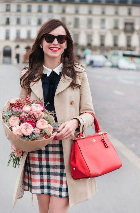Chica sosteniendo un ramo de flores y un bolso rojo