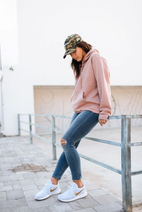 Chica usando jeans y sudadera de color rosa palo