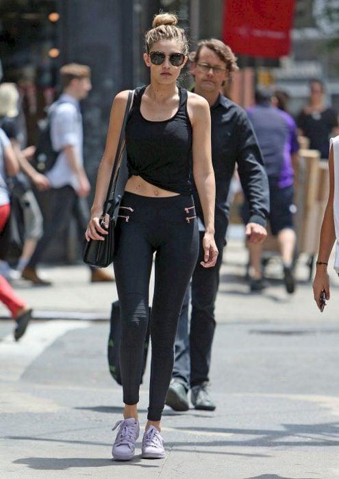 Gigi caminando por las calles de Los Ángeles usando leggings y top negro