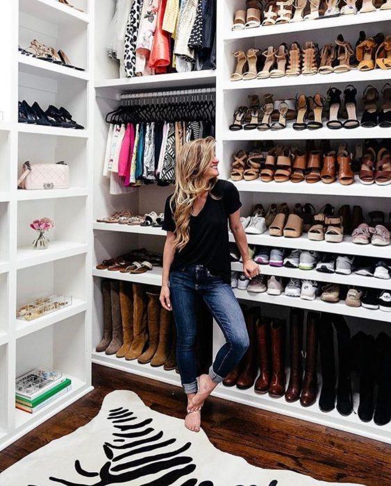 Chica viendo su guardarropa con cientos de zapatos y botas