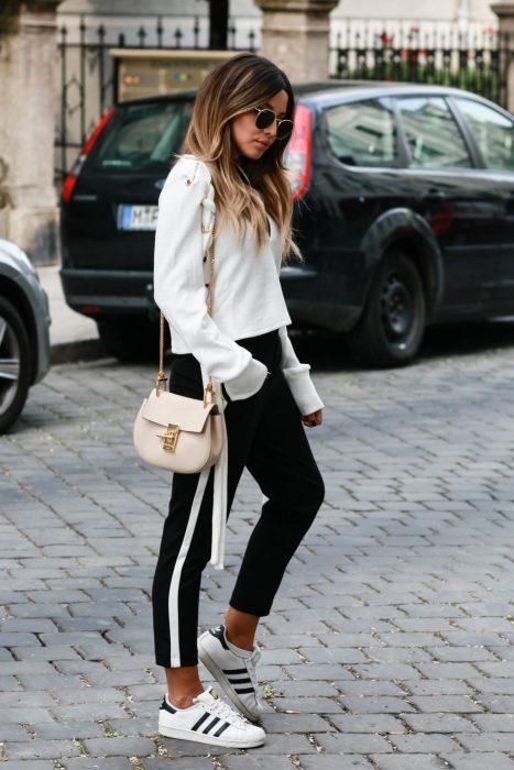 Chica usando pantalón negro, tenis adidas blancos y sudadera