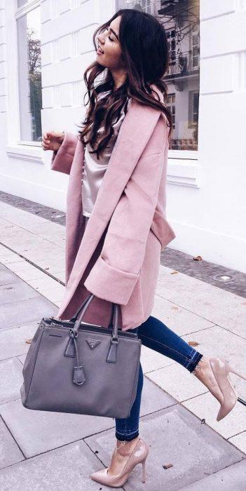 Chica usando unos stilettos y abrigo rosa con jeans