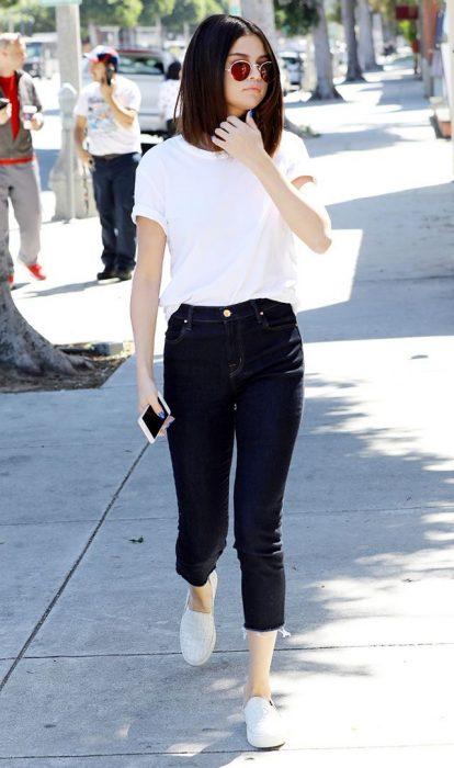Selena caminando por las calles usando jeans y camisa blanca