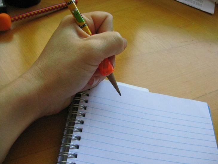 Persona zurda escribiendo en una libreta con aros