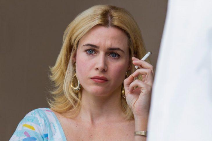 mujer rubia con cigarro y aretes