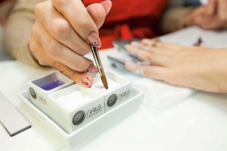Chica aplicando acrilico en las uñas de otra mujer