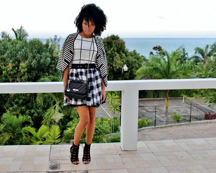 Chica usando una falda a cuadros, blusa de cuadros grandes y saco de líneas blancas con negro