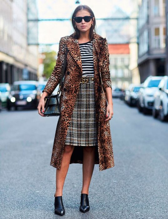 Chica usando una falda a cuadros, blusa a rayas y saco de animal print leopardo