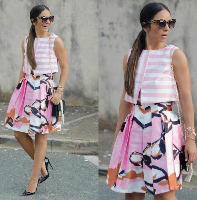 Chica usando un top rosa con líneas y una falda con flores en tonos rosa y negro