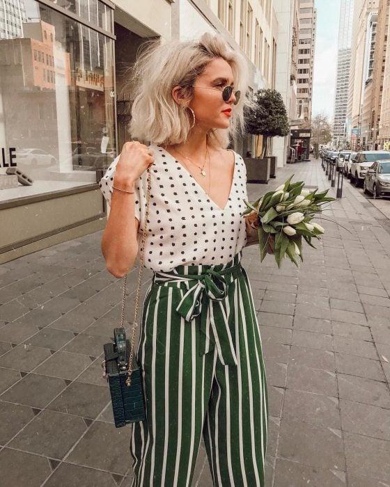 Chica usando un pantalón verde con líneas y una blusa blanca con puntos