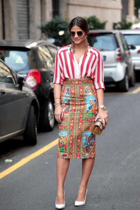 Chica usando una falda estampada con colores y un top de líneas rojas con bolso estampado y aretes de plumas