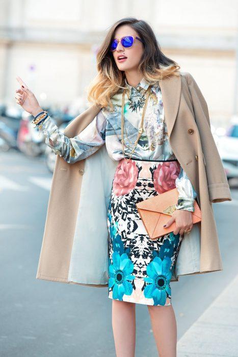 Chica parando un taxi usando un saco de color beige, falda de estampado floral y blusa con estampado de color gris