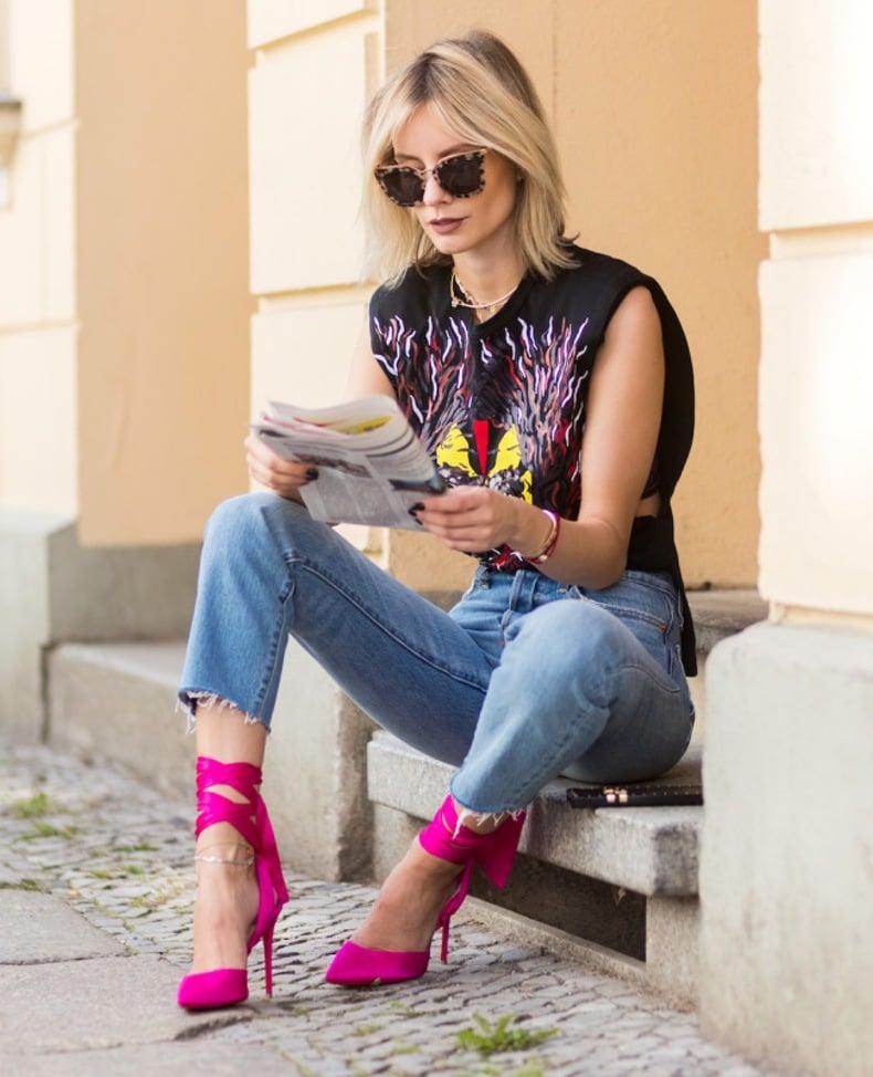 Chica sentada usando unos zapatos de color rosa
