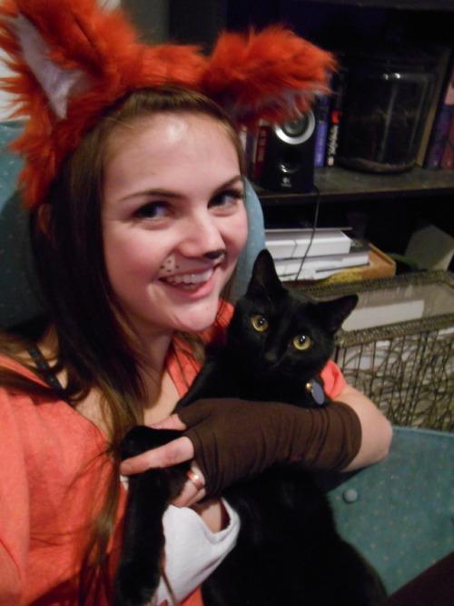 Chica disfrazada junto a su gato negro