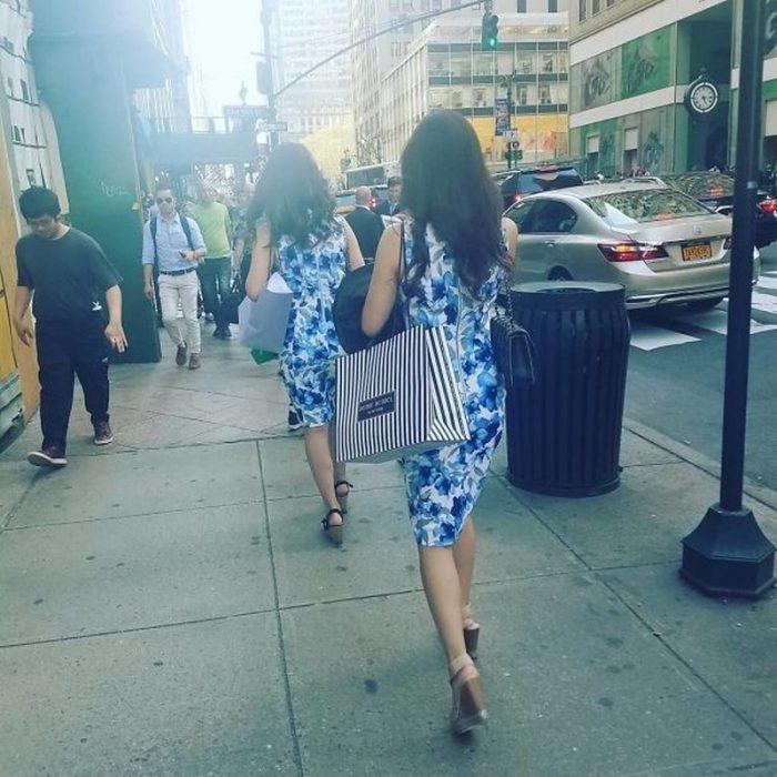 Dos mujeres desconocidas caminando en la calle con el mismo vestido