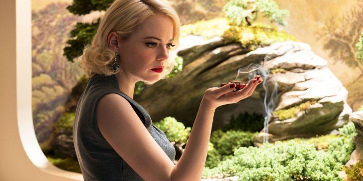 Emma Stone sujetando un carro de juguete mientras está frente a un cuadro