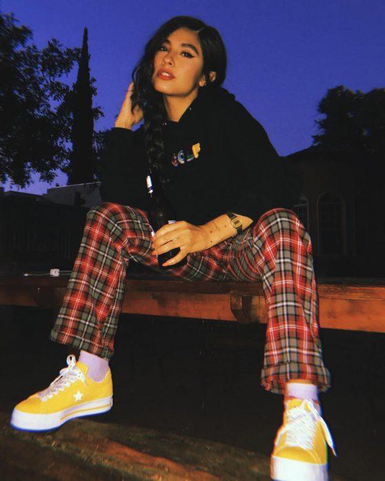 Mujer sentada con pantalón de rayas y cuadros