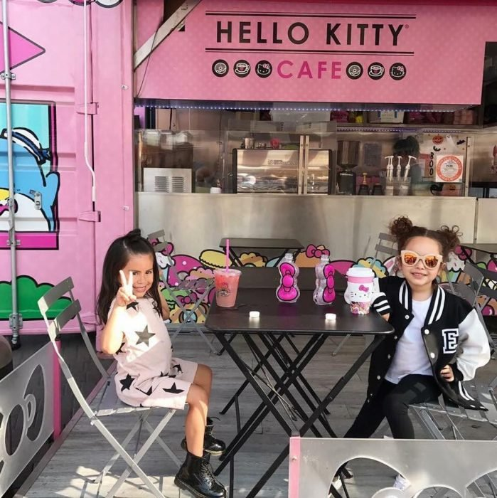 niñas sentadas en bancas y mesas en café rosa