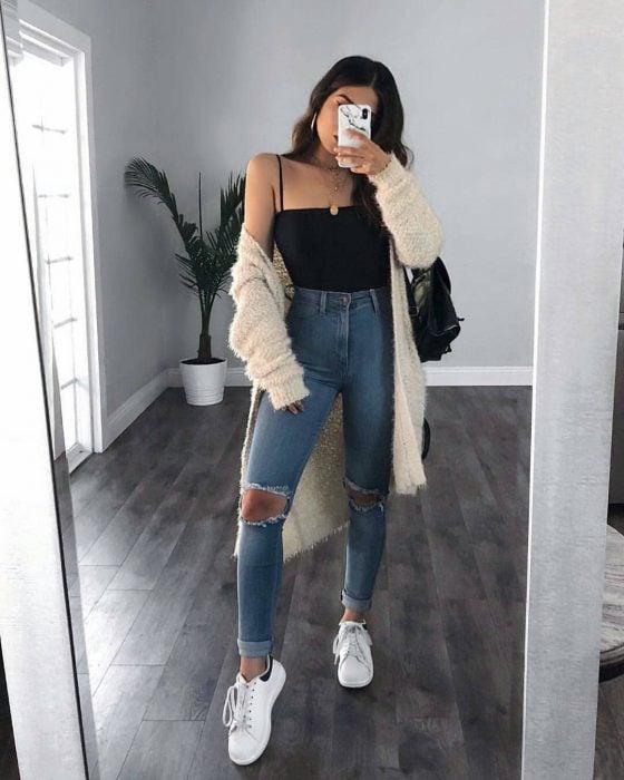 mujer con jeans tenis y sudadera