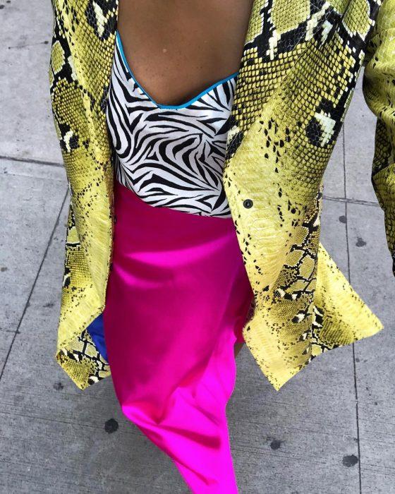 mujer con falda rosa y saco amarillo blusa de cebra