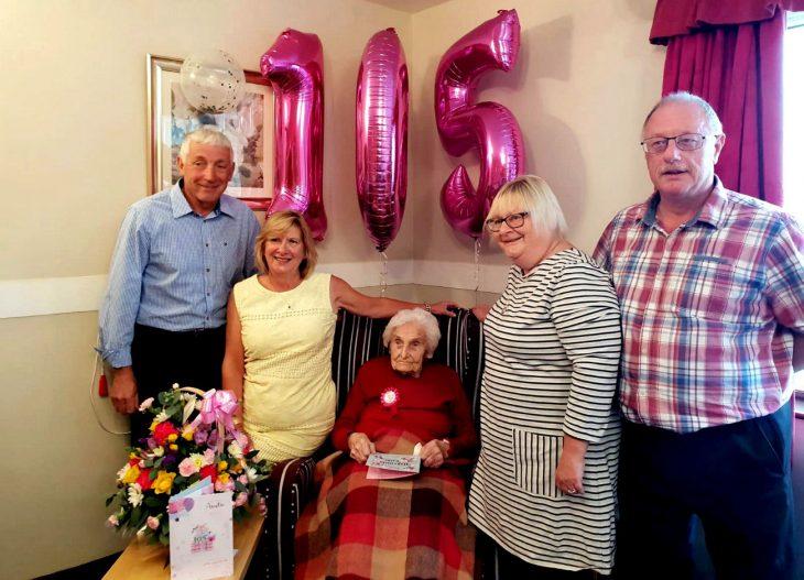 hombres y mujeres alrededor de anciana con globos de cumpleaños rosa