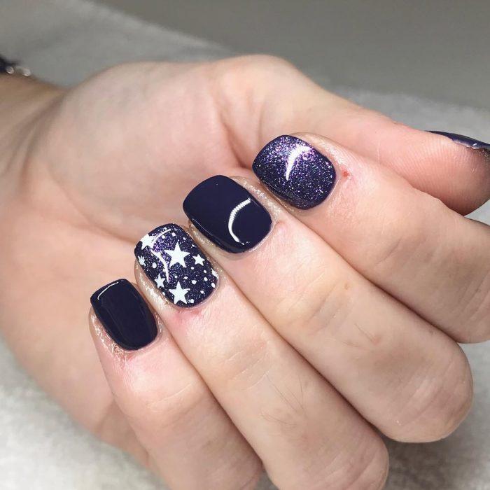 Manos con uñas negras de galaxia