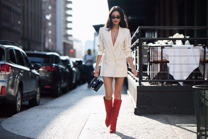 mujer con saco blanco y botas rojas