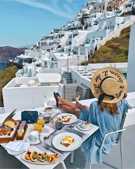 mujer con vestido azul sombrero de paja en grecia desayuno
