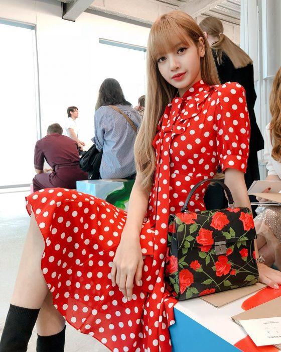 mujer con vestido rojo con puntos blancos y bolso negro con flores