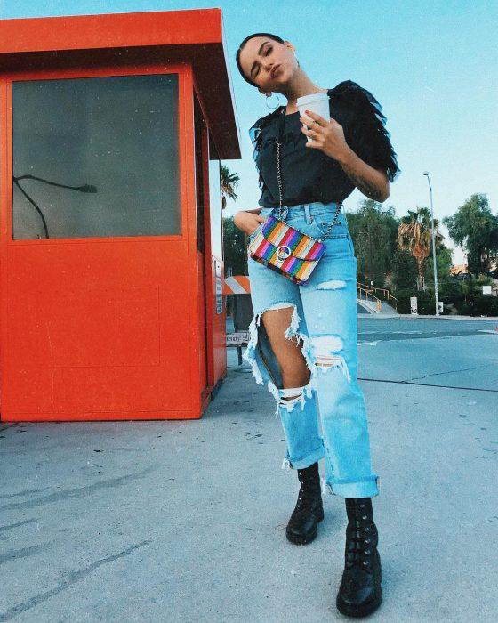 mujer con jeans de mezclilla y blusa negra de hombreras